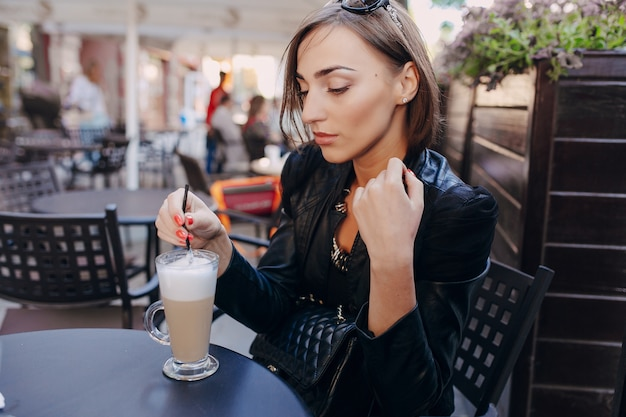 Kobieta pije kawę ze słomką