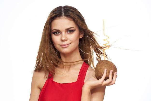 Kobieta pije koktajl kokosowy przez słomkowy styl życia czerwona koszulka jasnym tle.