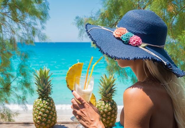 Kobieta pije koktajl w barze na plaży