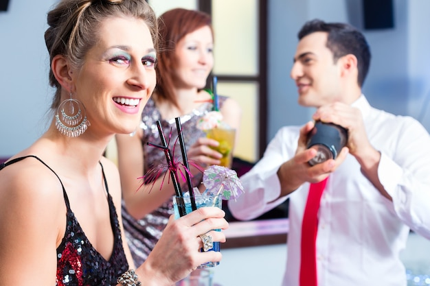 Kobieta pije koktajle w eleganckim klubie nocnym