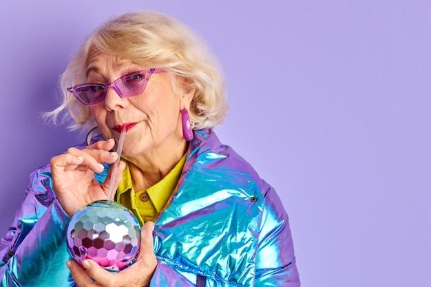 Kobieta pije napój z kolorowej butelki, czas na imprezę