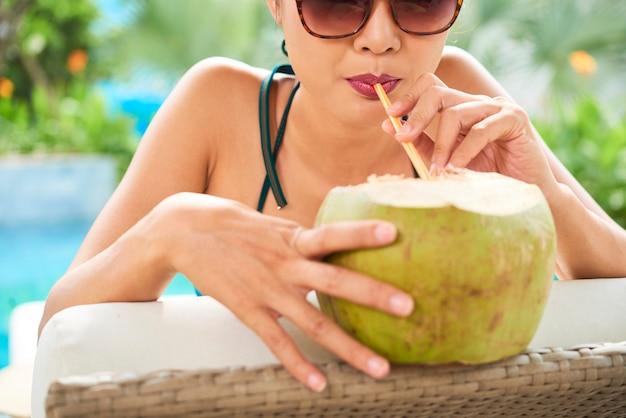 Kobieta pije orzeźwiający koktajl kokosowy