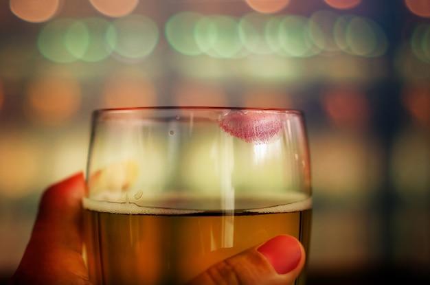 Kobieta pije piwnego pojęcie. szklanka piwa z marką red lipstick. kobiecy nastrój