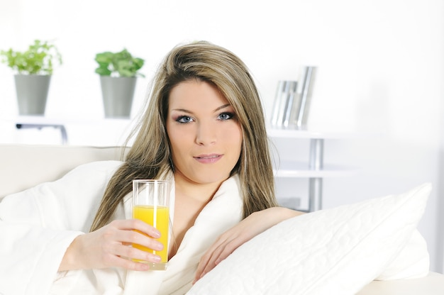 Kobieta pije sok pomarańczowego i relaksuje na białej kanapie