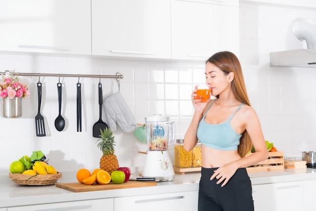 Kobieta pije soki owocowe i warzywne.