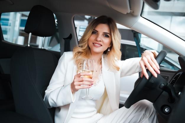 Kobieta pije szampana w samochodzie