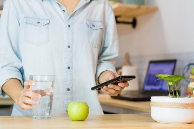 Kobieta pije wodę podczas korzystania z telefonu komórkowego