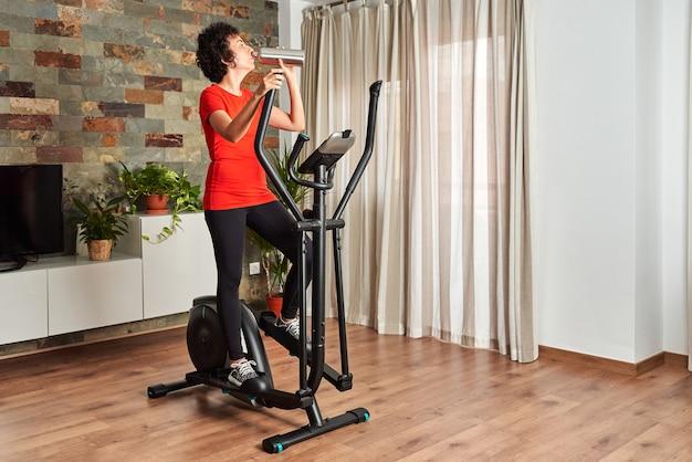 Kobieta pije wodę podczas treningu w domu na orbitreku w salonie