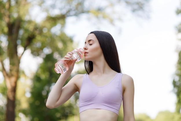 Kobieta pije wodę z butelki po treningu w parku, aby zachować nawodnienie.