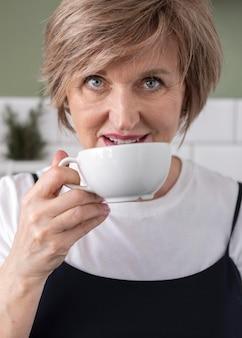 Kobieta pije z filiżanki z bliska