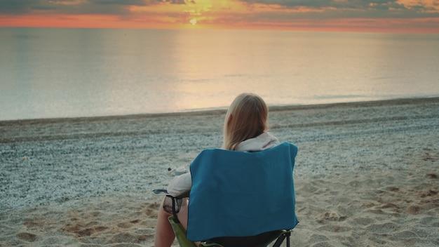 Kobieta pije z kubka termicznego i siedzi na plaży przed wschodem słońca