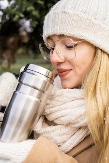 Kobieta pije z termosu w parku w zimie