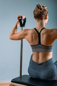 Kobieta pilates w reformatorze cadillaca robi ćwiczenia rozciągające na siłowni. koncepcja fitness, specjalny sprzęt fitness, zdrowy styl życia, plastik. skopiuj miejsce, baner sportowy na reklamę