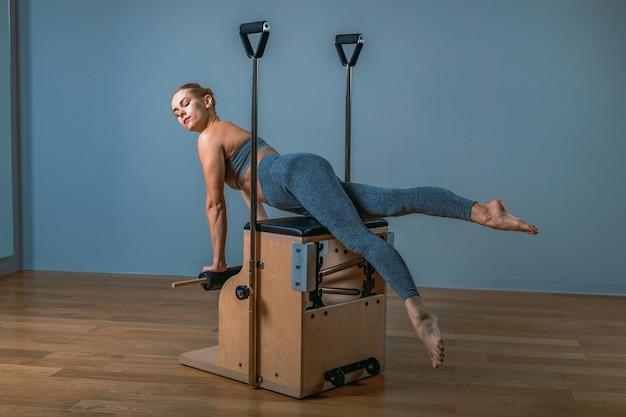 Kobieta pilates w reformatorze robi ćwiczenia rozciągające na siłowni. koncepcja fitness, specjalny sprzęt fitness, zdrowy styl życia, plastik. skopiuj miejsce, baner sportowy do reklamy.
