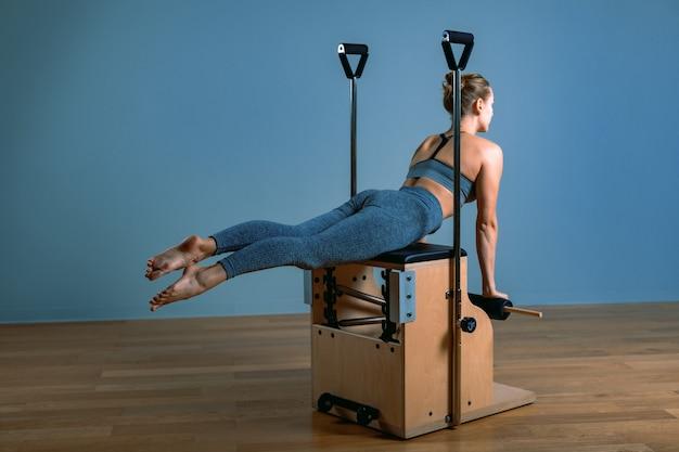 Kobieta pilates w reformatorze robi ćwiczenia rozciągające na siłowni. koncepcja fitness, specjalny sprzęt fitness, zdrowy styl życia, plastik. skopiuj miejsce, baner sportowy na reklamę