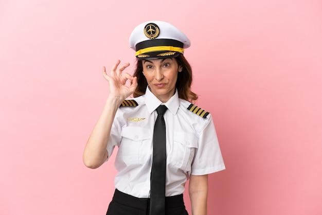 Kobieta pilot samolotu w średnim wieku na białym tle na różowym tle pokazując znak ok palcami