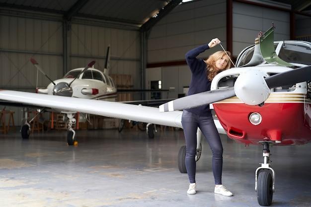 Kobieta pilot w hangarze wykonująca konserwację silnika małego samolotu