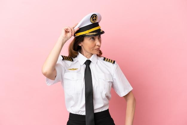 Kobieta pilotka samolotu w średnim wieku na białym tle na różowym tle, mająca wątpliwości i zdezorientowany wyraz twarzy