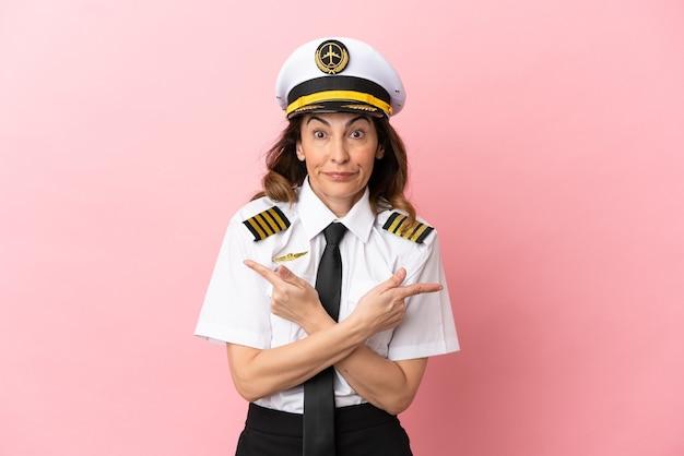 Kobieta pilotka samolotu w średnim wieku na białym tle na różowym tle wskazująca na boki mające wątpliwości