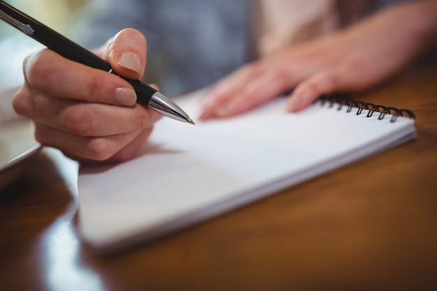 Kobieta pisania na notatnik
