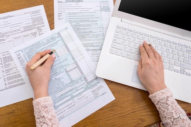 Kobieta pisząca na laptopie i wypełniająca formularz 1040