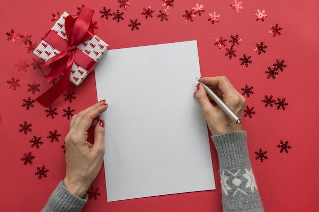 Kobieta pisze cele, listę kontrolną, plany i marzenia na nowy rok. lista życzeń na boże narodzenie. lista rzeczy do zrobienia
