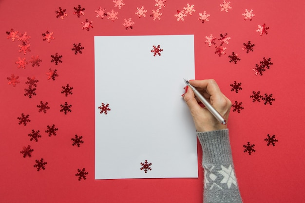 Kobieta pisze cele, listę kontrolną, plany i marzenia na nowy rok. lista życzeń na boże narodzenie na czerwonym świątecznym wystroju.