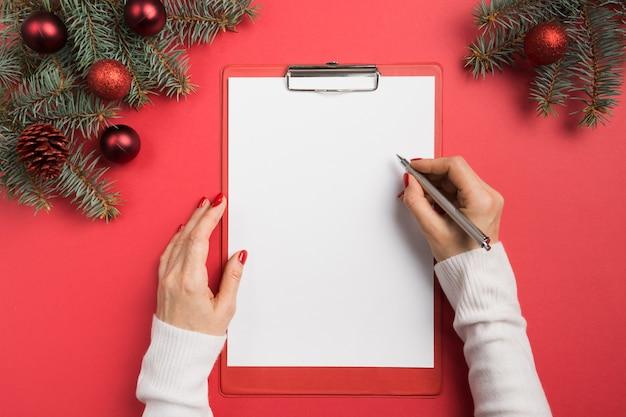 Kobieta pisze cele, listę kontrolną, plany i marzenia na nowy rok. lista życzeń na boże narodzenie. widok z góry