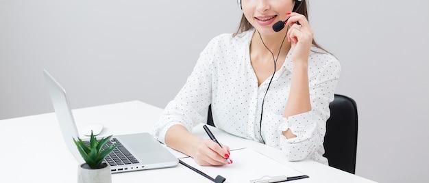 Kobieta pisze coś podczas rozmowy z kimś na zestawie słuchawkowym