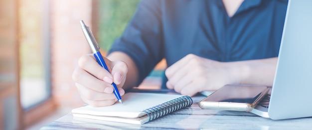 Kobieta pisze długopisem w biurze na notatniku, na stole telefony komórkowe i laptopy, baner internetowy.