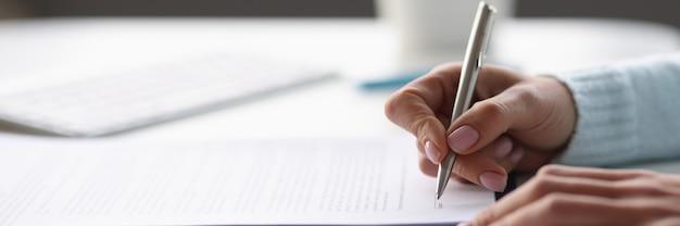 Kobieta pisze długopisem w dokumentach przy stole w domu zbliżenie praca zdalna z papierami