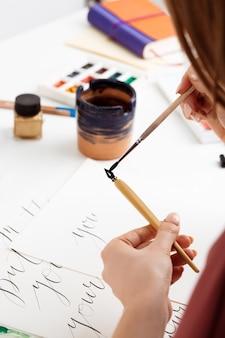 Kobieta pisze kaligrafia na pocztówkach