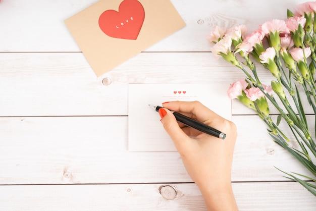 Kobieta pisze list miłosny na białym papierze z figurami w kształcie czerwonego serca. ręcznie wykonana pocztówka na obchody świętego walentego. wysyłaj listy do swoich kochanków i przyjaciół 14 lutego