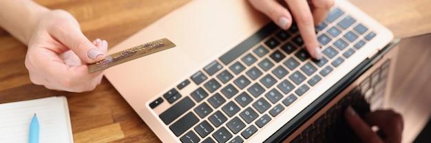 Kobieta pisze na klawiaturze laptopa i trzyma zbliżenie karty kredytowej banku