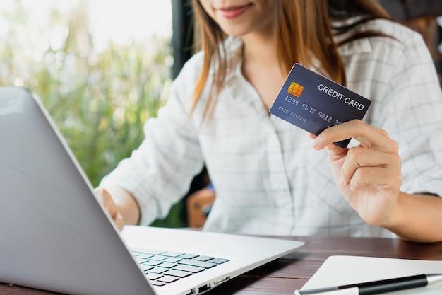 Kobieta pisze na klawiaturze laptopa, trzymając w ręku koncepcję biznesową, technologię i styl życia kart kredytowych
