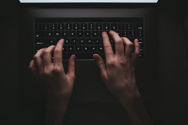 Kobieta pisze na klawiaturze laptopa