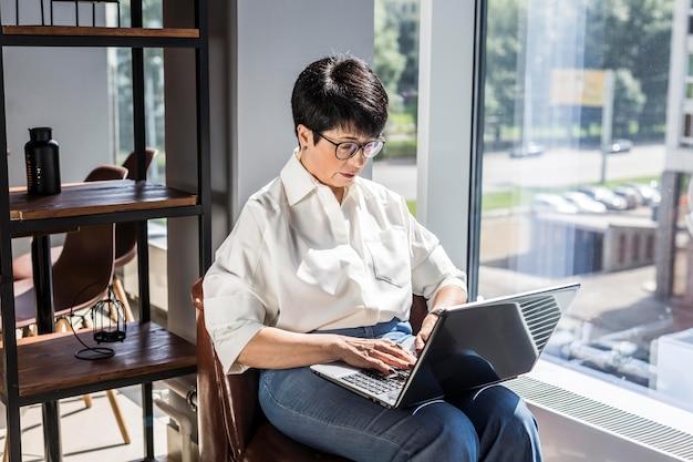 Kobieta pisze na maszynie i pracuje w pomieszczeniu