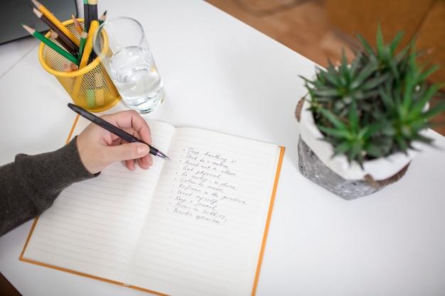 Kobieta pisze na notatniku listę zasad dotyczących zdrowia psychicznego