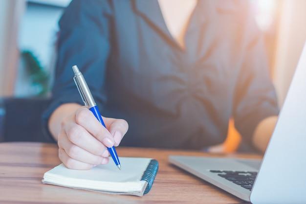 Kobieta pisze na notatniku piórem i używa laptopa do pracy w biurze.