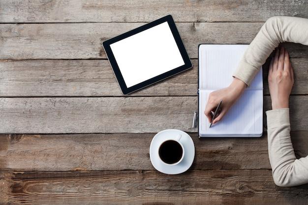 Kobieta pisze na papierze z ekranem cyfrowego tabletu obok niej. górny kąt