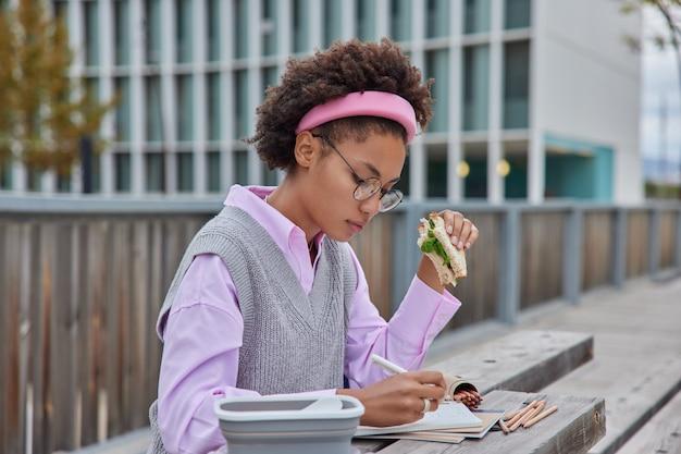 Kobieta pisze notatki w zeszycie zapisuje pomysły edukacyjne na studia praca przygotowuje pouczające badania odrabia pracę domową je smaczną kanapkę pozuje na zewnątrz na tle drapaczy chmur