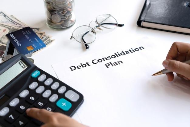 Kobieta pisze plan konsolidacji zadłużenia na papierze podczas korzystania z kalkulatora na biurku. skopiuj przestrzeń, z bliska.