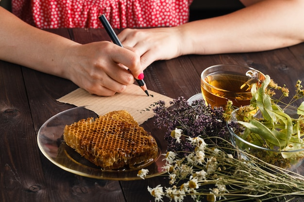 Kobieta pisze przepis na herbatę ziołową.