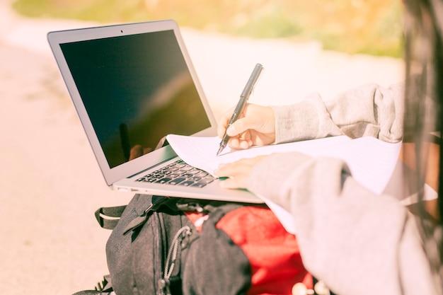 Kobieta pisze ręcznie na notebooku w słoneczny dzień