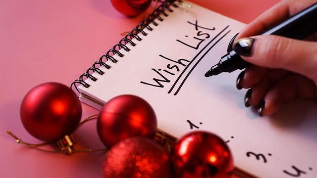 Kobieta pisze swoją listę życzeń. świąteczny wzór na różowym tle z czerwonymi bombkami