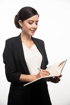 Kobieta pisze w notatniku na białej ścianie.