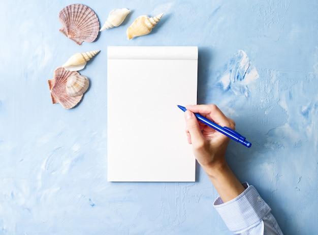 Kobieta pisze w notatniku na kamiennym błękita stole, rama seashell, odgórny widok