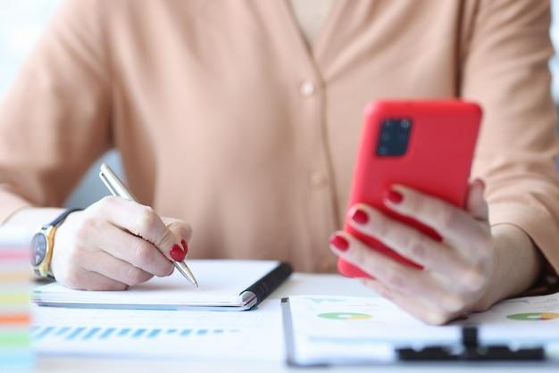 Kobieta pisze w notesie i trzymając telefon komórkowy w ich rękach zbliżenie