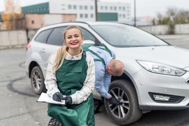 Kobieta pisze w schowku podczas mocowania koła pracownika