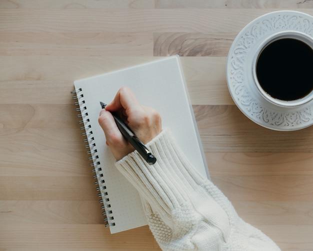 Kobieta pisze w zeszycie na drewnianym stole, ręka w swetrze, trzymając pióro, szkicownik, rysunek, widok z góry